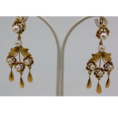 long gold earrings with cultured pearls.