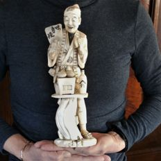 A well carved large ivory okimono of a clams salesman, signed (ca. 32cm) - Japan - ca. 1910 - 1920