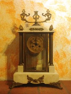 Clock in brass and Carrara marble with four columns and two crystal doors. Circa 1880
