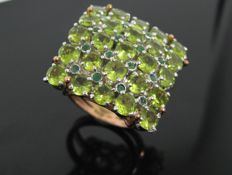 14 kt rose gold and silver 800 big ring set with 55 peridots round-cut tot 13,75 ct and 16 emeralds round -cut ct 0,64 tot.