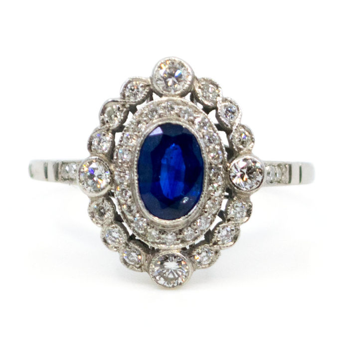Elegant Art-Deco inspired ring featuring 0.90ct Sapphire surrounded by 0.50ct (mixed 0,05 to 0,01ct, K S1) Brilliant Cut Diamonds in Platinum.