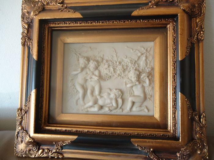Large alabaster plaque in a painting frame behind glass, with four Cherubim angels in Garlands and rose, in a black gilded frame