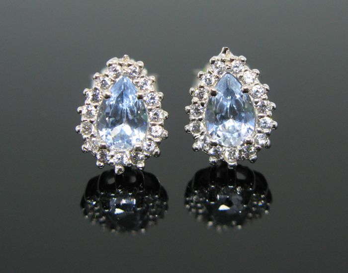 18 kt white gold, halo earrings, set with 2 aquamarine pear-cut tot 0,70 ct and 30 white zircon brillant-cut ct 0,60 tot.