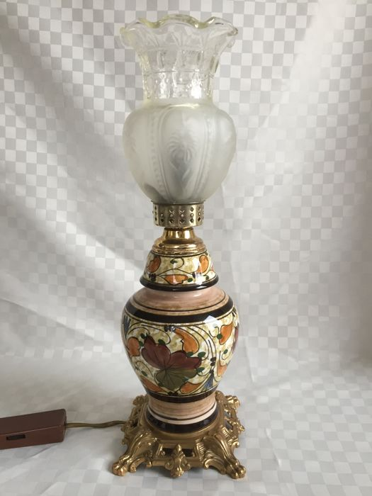 Electric oil lamp with carved glass lampshade and ceramics in the middle portion, brass foot.