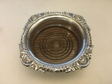 Vintage solid silver Embossed Decorated rim & Mahagany Base bottle coaster . London- 1900. Maker- Thomas Bradbury & Son