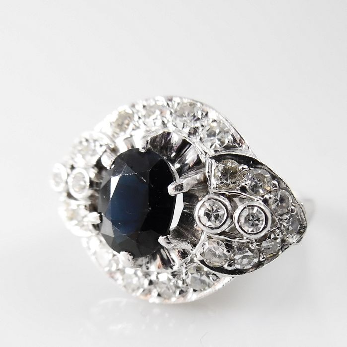 18 kt handmade white gold ring with 26 diamonds of 1.00 ct in total and a blue sapphire of 1.40 ct