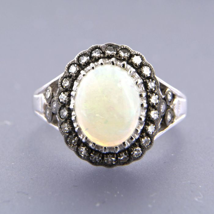 14 kt white gold entourage ring with 1.40 ct cabochon oval cut white opal and 28 diamonds, ring size 17.25 (54)