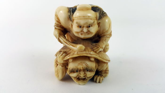 "Ivory Okimono, Sennin riding on a turtle shell under which is hiding a Oni, Signed ""Masanao (of Kioto)  - Japan - ca. 1920-1930"