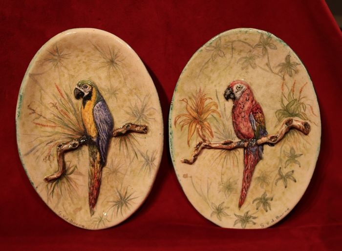 A pair of glazed earthenware Art Deco relief wall plaques decorated with parrots