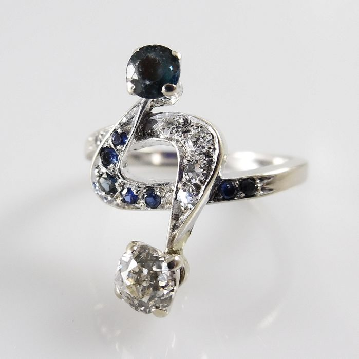 18 kt white gold ring with 1 old European cut diamond and 6 others and blue sapphires