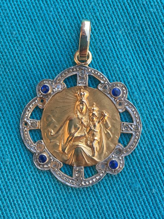 Medal pendant in gold and platinum details with the representation of the Virgin of Carmen surrounded by rose cut diamonds 3/3 and blue rubies, year c.1930
