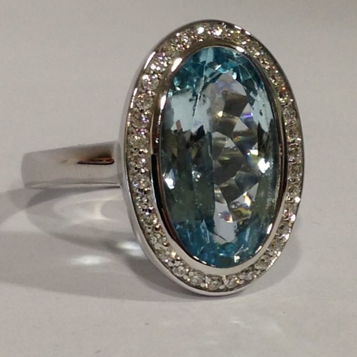 14 kt white gold ring with topaz, surrounded by diamonds.
