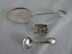 3 Pieces of antique silver, including a wet fruit scoop, sauce spoon, and a tea strainer - the Netherlands and Europe - last quarter 19th century and 1905