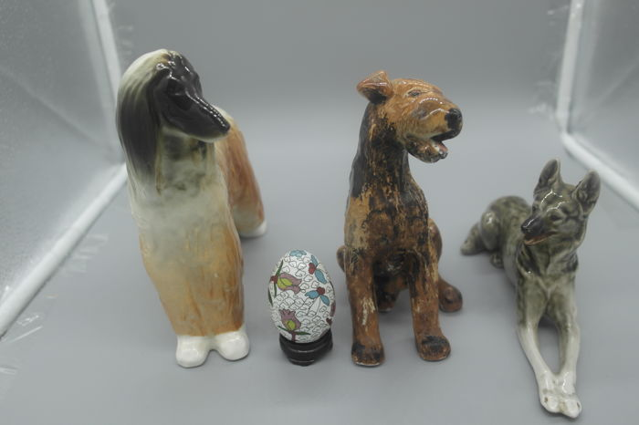 Three Lomonosov porcelain figurines of Afghan, Airedale and Alsatian dogs