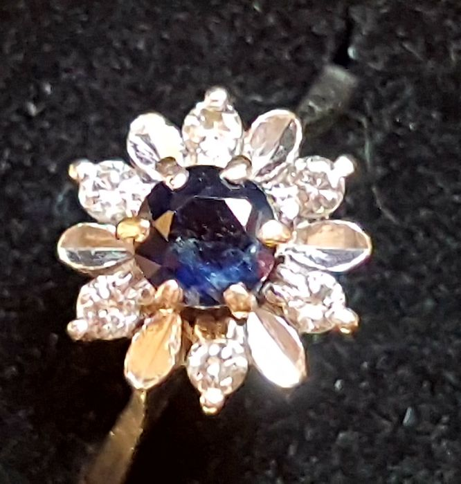 1950s − Natural brilliant cut sapphires weighing 0.55 ct, set at the centre of a white gold flower, with 6 natural brilliant cut diamonds totalling 0.10 ct, old mine cut, colour H/I