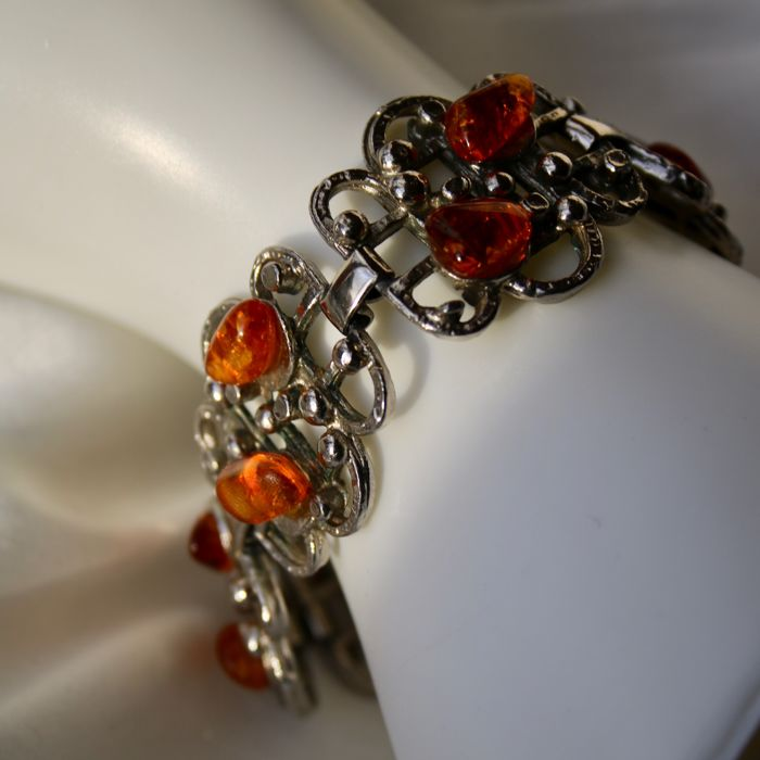 Handcrafted heavy silver bracelet decorated with 12 cabochon cut honing Ambers.