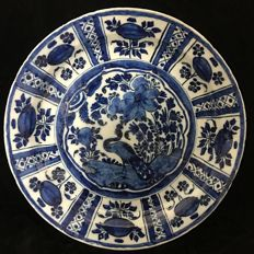 Large blue dish with a decor of flowers and a peacock in WanLi decor, Delft, The Netherlands, circa 1700