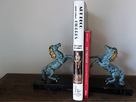A set of bookends with bronze horses on a marble base