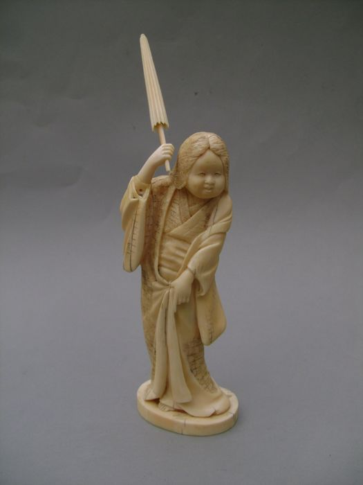 Okimono in carved ivory. Okame and her sunshade. Signed UNGYOKU - Japan - End of 19th/beginning of 20th century