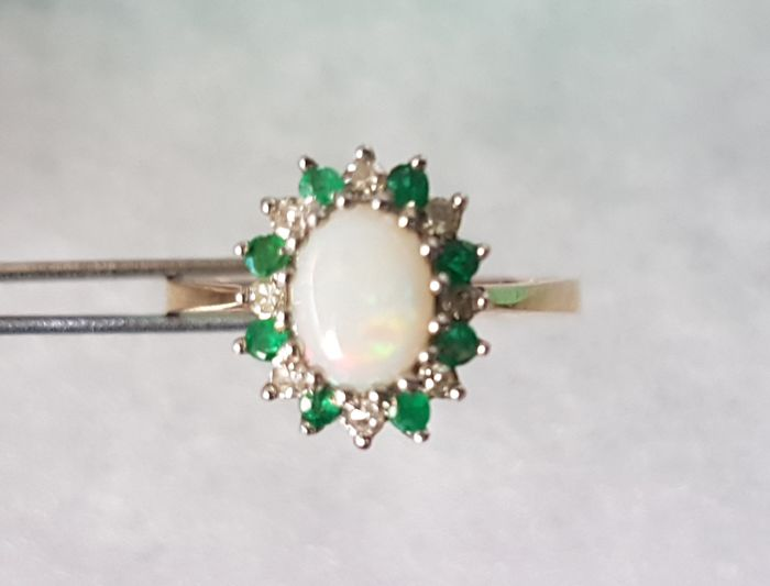 Ring by D. S&c.   -London- 1971, 1.5 ct opal cabochon, 7 natural brilliant cut diamonds, VVS2/F, totalling 0.035 ct, 7 natural brilliant cut emeralds totalling