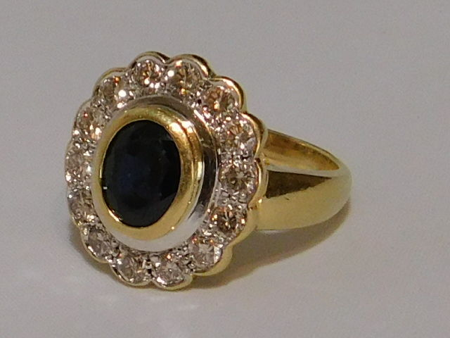 18 kt gold ring with oval sapphire of 2 carats surrounded ...