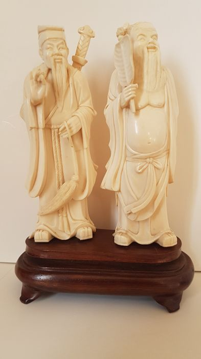 Two finely carved Chinese ivory 'immortals' on a wooden pedestal - China - around 1930