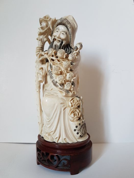 A finely carved ivory figure of an 'immortal' with a stick and flowers, on a wooden pedestal - China - around 1930/40