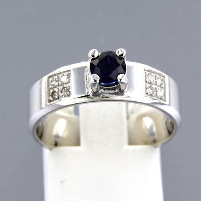 14 kt white gold ring, set with a round cut sapphire and a diamond, ring size 17 (53)