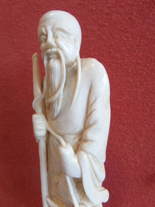 Ivory sculpture of a fisherman with a catch on wooden pedestal - China - early 20th century