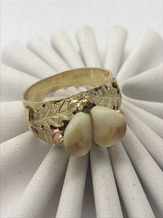 Hunting trophy ring with deer teeth surrounded by 4 oak leaves
