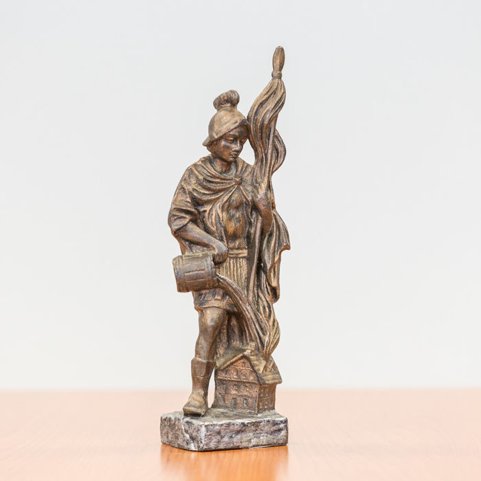 Bronze sculpture of a firefighter with a standard