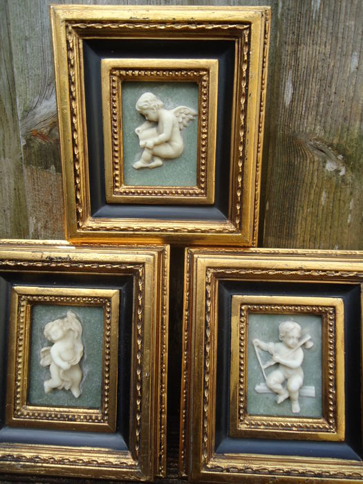 three alabaster putti paintings in gold coloured baroque frames