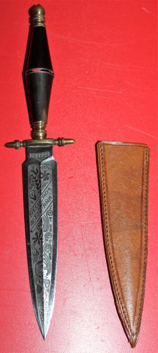 Spanish dagger, marked : Toledo - Recuerdo de Espana, with leather sheath and decorated blade, in good condition