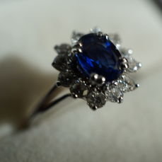 Ring with entourage, natural central sapphire, 12 brilliants in offset around.