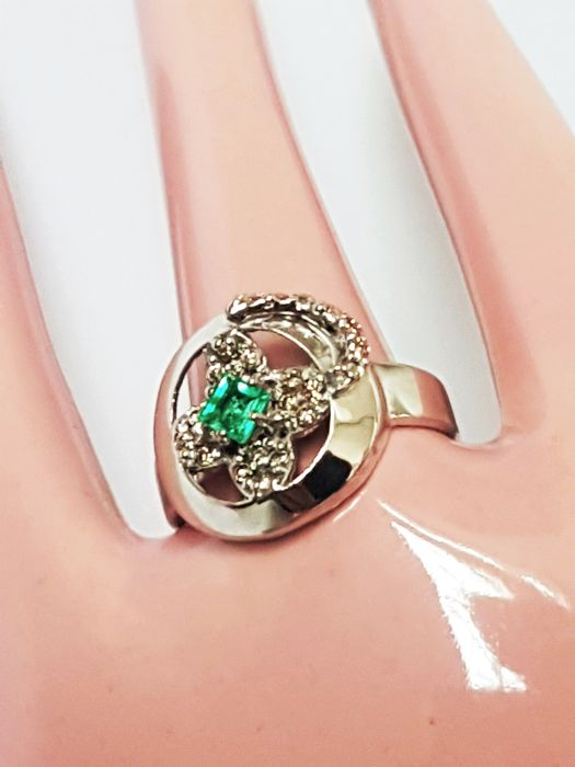 Women's ring of 18 kt white gold 3.3 g with emerald stone 0.16 ct and 23 brilliant cut diamonds 0.18 ct