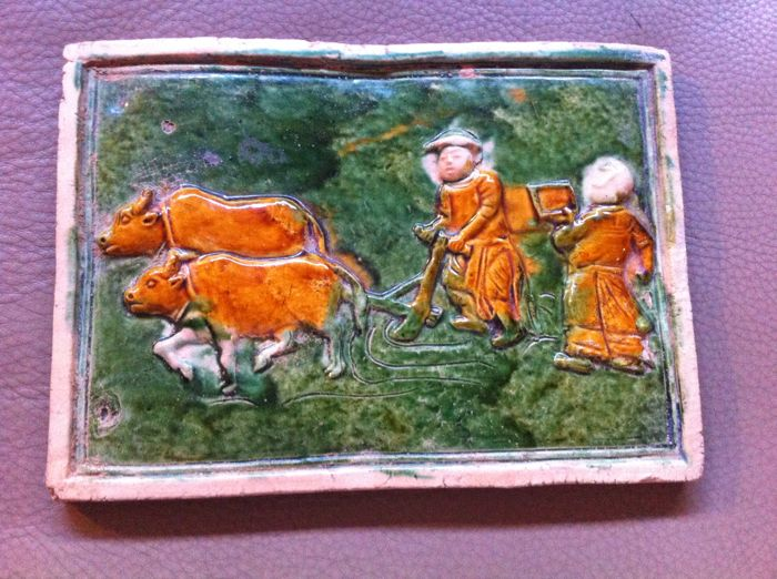 Plaque in sandstone in the TANG style, depicting two people, one working with two oxen, iridescent glazing in green and ochre - China - late 20th century