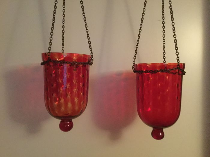 A pair of hanging candle holders in glass with metal chain
