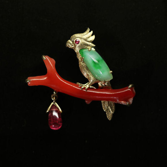 18Kt  pendant in the shape of a bird on a branch, set with 1.01 ct of  Jadeite,  4.41 ct. of red coral (Aka) and 1.16 ct. of Ruby