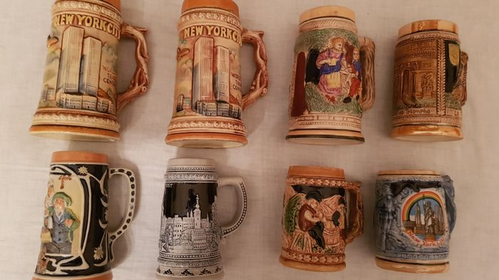 Interesting lot of 8 different types of ceramic beer mugs with figural decorations in relief