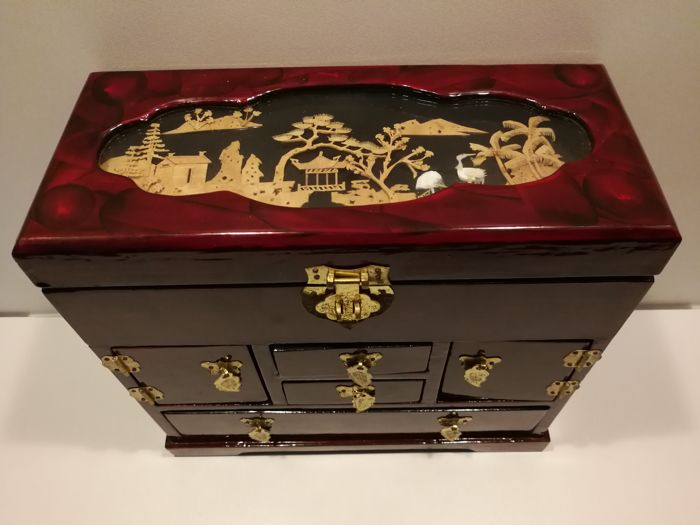 Large Oriental Jewellery Cabinet In Red Lacquer With Cork Art Work.