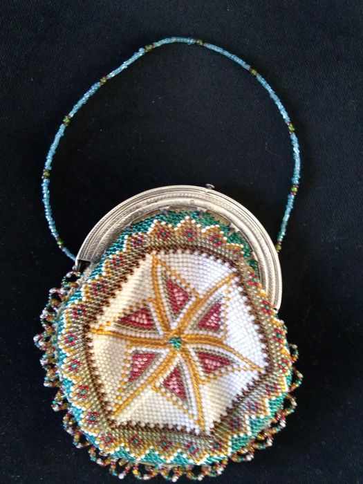 Beaded purse with silver brace.