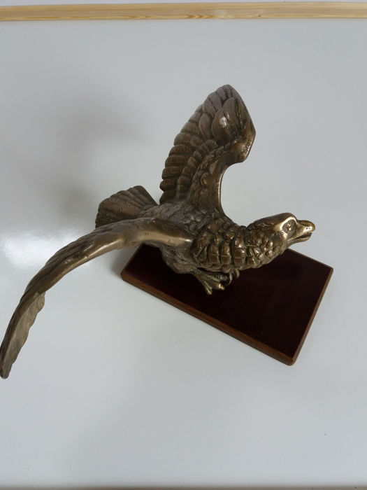 Eagle with spread wings made of copper/brass on a wooden stand