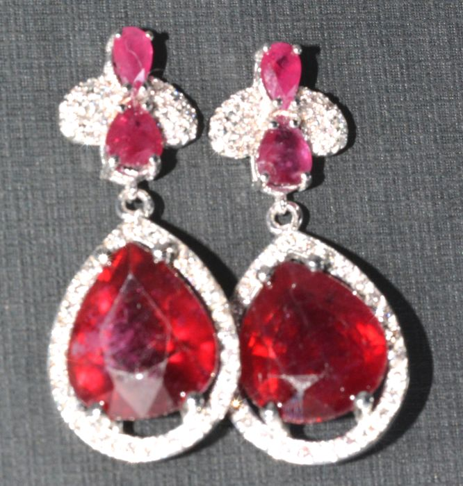 18 kt. Exclusive evening earrings with large pear-shaped blood red Rubies weighing 16.60 ct. and accompanied by 74 brilliant cut GH diamonds weighing 0.40 ct. Length: 31.10 mm. *** no reserve price ***