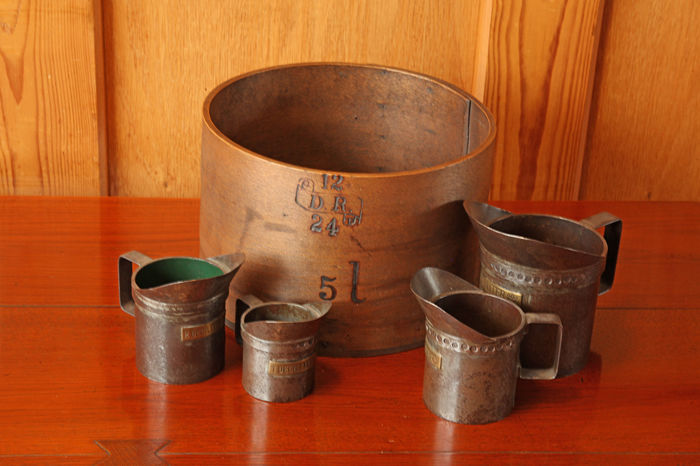 4 Liquid measuring cups and a wooden grain size - ca. 1900