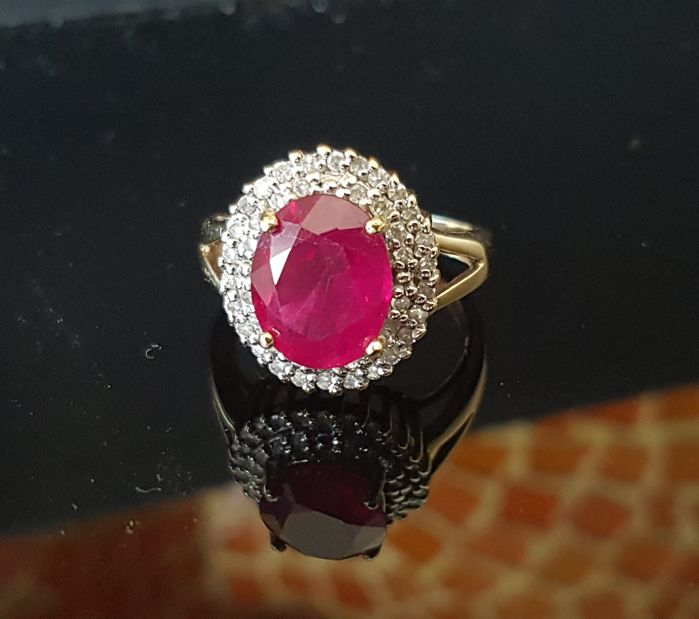 14 kt gold ring with central 10.5 x 8.5 mm oval cut ruby of 2.32 ct and 52 SI diamonds in round cut each of 0.9 - 1.2 mm with a total of 0.34 ct, ring size 15.8 mm, weight 4.9