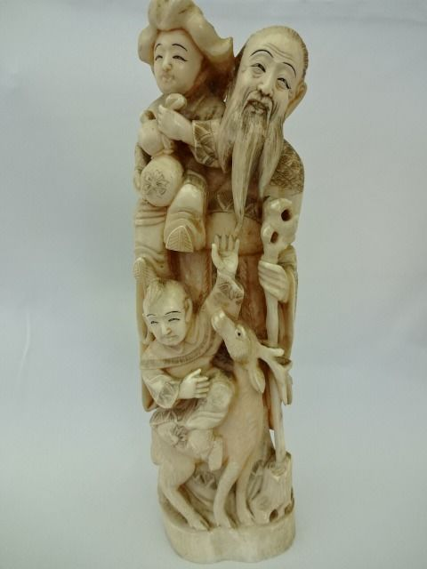 Carved ivory okimono - Old wise man with staff, deer and two karako - Signed - Japanese - Meiji period (1868–1912)