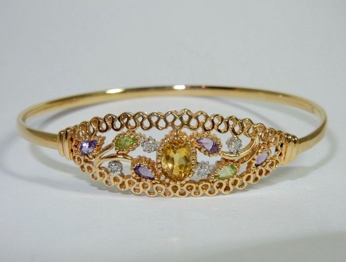 """14 kt gold cocktail bracelet with a citrine, diamonds, peridots and amethysts. Signed """"Aj""""."""