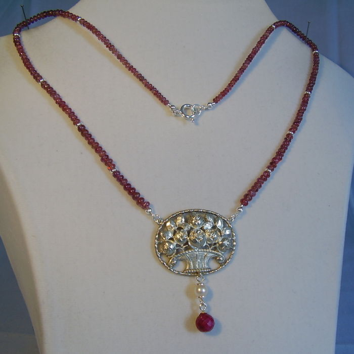 Necklace with silver flower basket on polished ruby roundels of 70 ct in total.