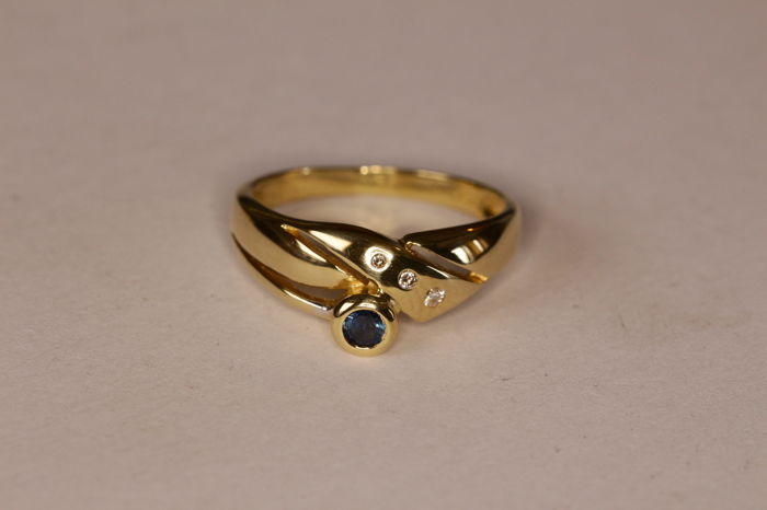 Contemporary 18 kt yellow gold ring set with a sapphire and brilliant cut diamonds