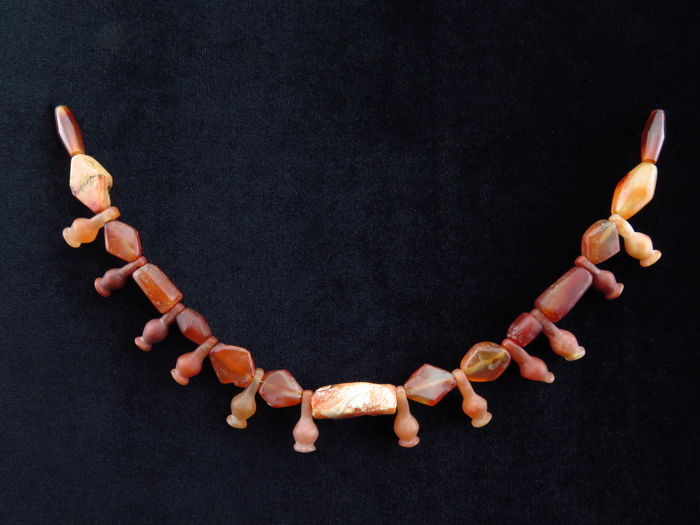 Egyptian necklace of carnelian beads and Poppy amulets on a board - 26 cm